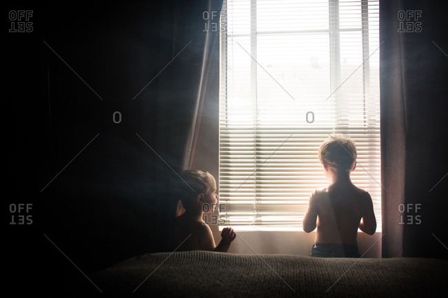 Smoke surrounding two boys looking out window