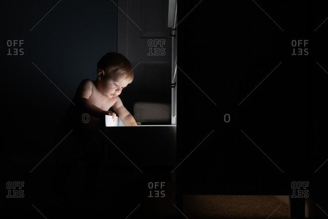 Little boy looking into illuminated drawer
