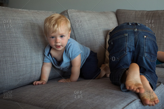 Two toddler boys playfully wrestling on a sofa