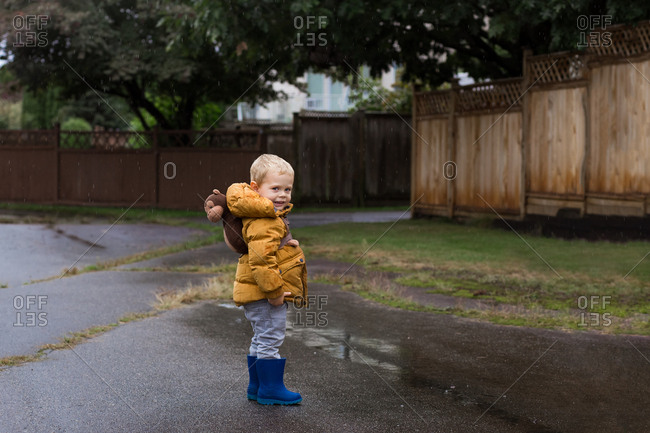 Little boy wearing yellow jacket and monkey backpack in the rain