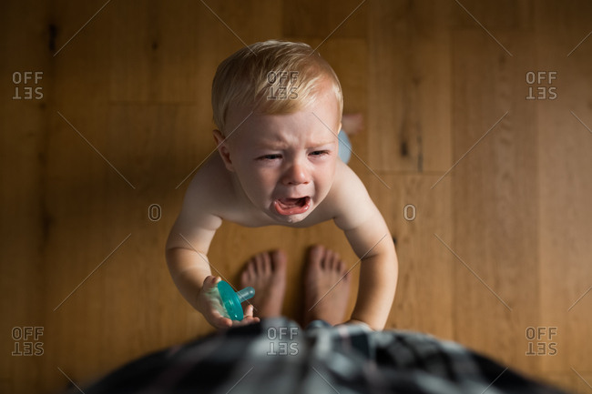 Overhead view of crying baby at mother's feet holding pacifier