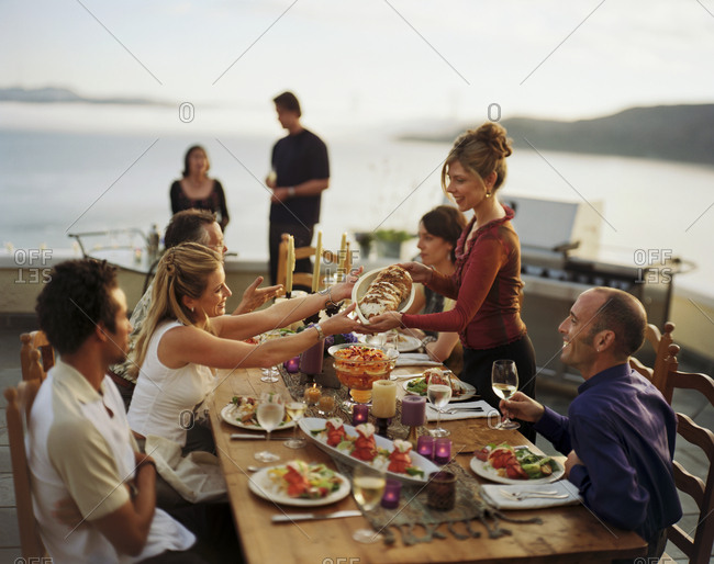 Woman handing another woman a dish of bread while seated around an outdoor dining table on a balcony with friends.