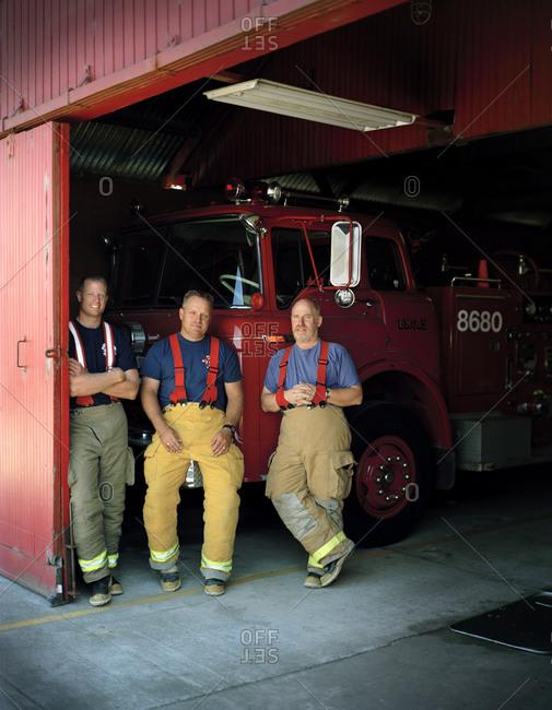 Three firemen back resting on a fire truck.