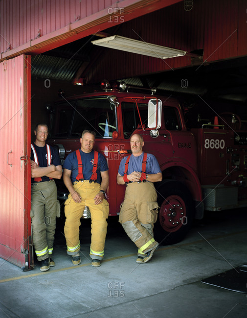 Three firemen back resting on a fire truck.