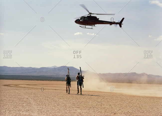 Adventurous young couple carrying sports equipment on their backs underneath hovering helicopter while running across a desert.