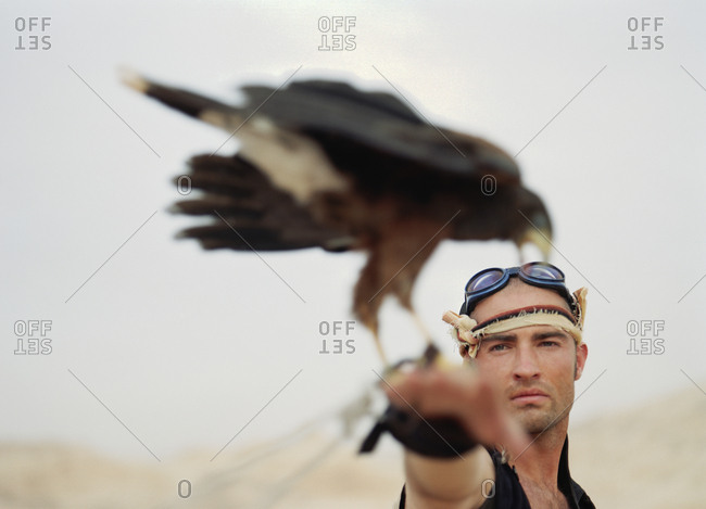 Young man standing with a bird of prey perched on his wrist.