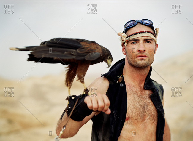 Portrait of an adventurous young man holding a bird of prey on his wrist while standing in a desert.