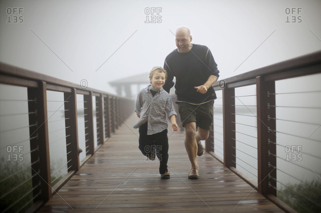 Mid-adult man having fun running along a misty pier with his young son.