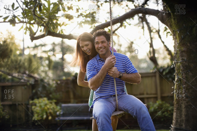 Mid-adult couple swinging on a rope in the garden.