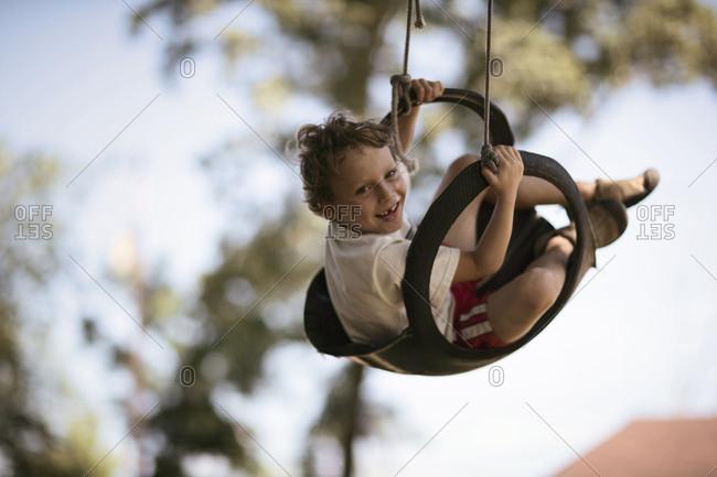 child swings in tire swing