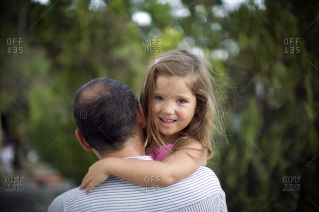 A small girl smiles as she is held by her father.