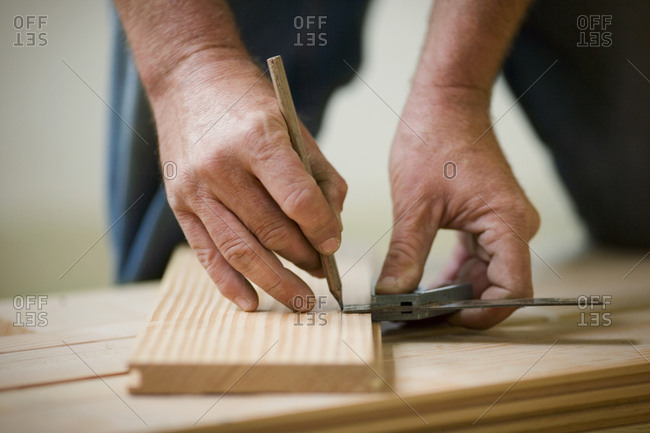 Hands of a male builder measuring a door and marking it with a pencil.