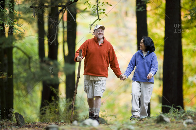 Mature couple hiking through a forest.