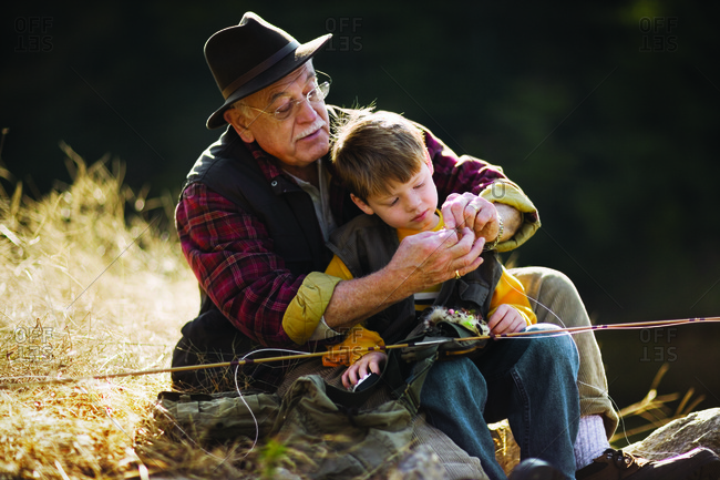 Senior man teaching his grandson how to fish.