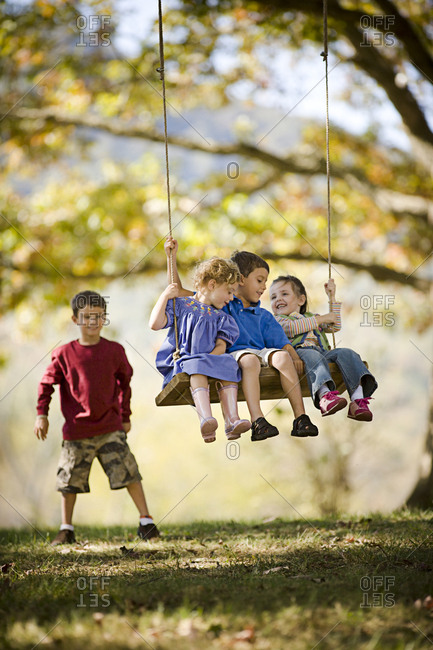 Three young siblings having fun on a swing together while their older brother pushes them in a grassy field.