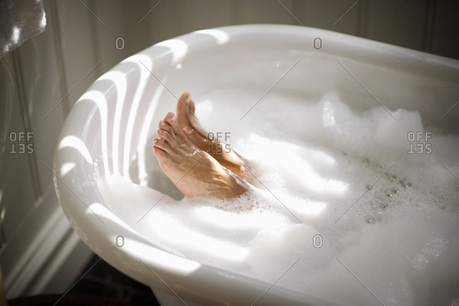 Feet of a woman in a bubble bath.