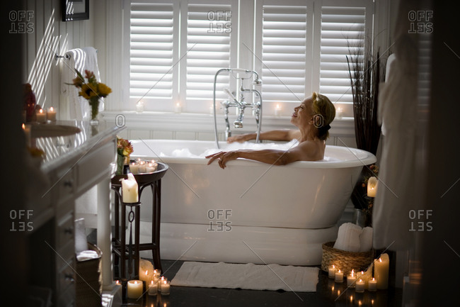 Mid-adult woman relaxing in a bubble bath surrounded by candles.