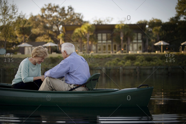 Happy senior couple holding hands while in a canoe.