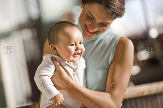 Happy young woman holding her smiling baby.