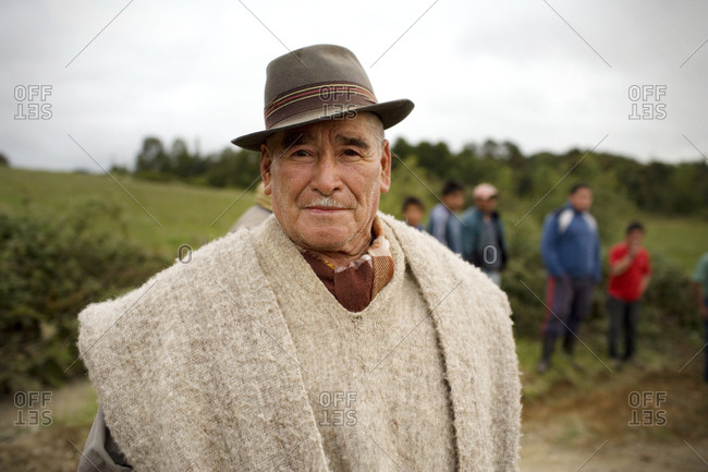 Portrait of a senior man wearing a poncho and a hat.