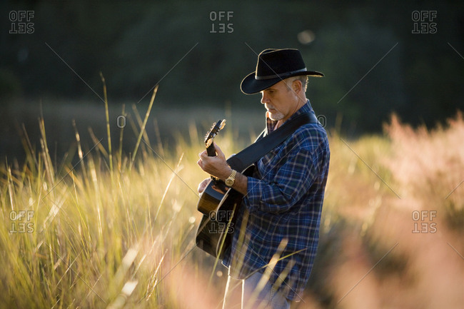 Mature man wearing a hat and strumming an acoustic guitar outdoors.