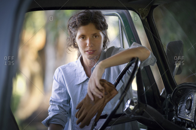 Front view of a young woman near a car.