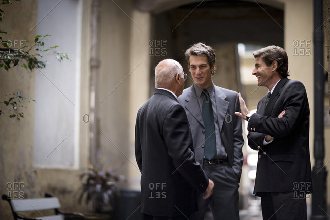 View of three businessmen in conversation.