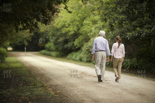 View of a young girl strolling with her grandfather.