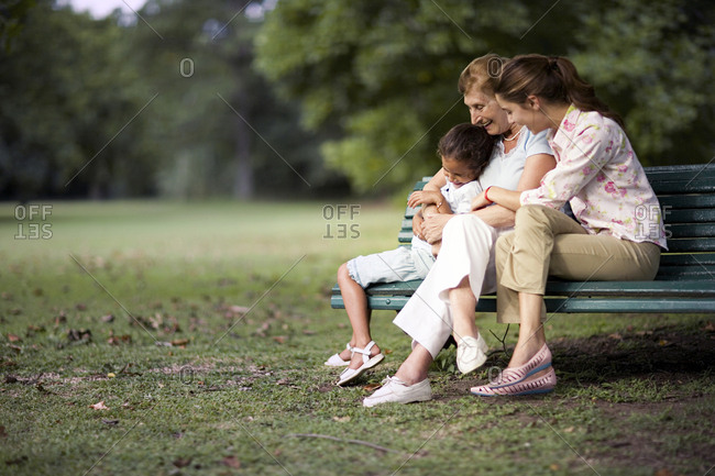 A family seen seated together on a bench.