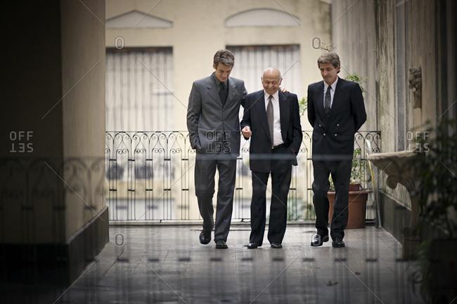 View of three men walking in a balcony.