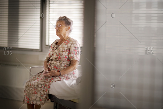 Portrait of an aged woman sitting on a bed.