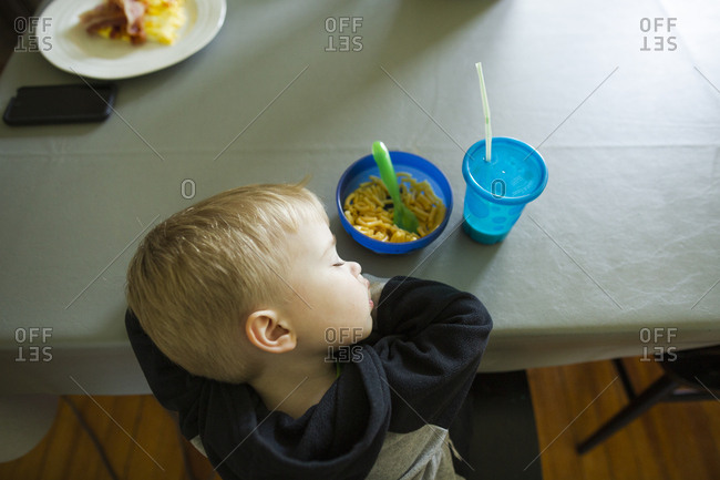 Overhead view of toddler boy who fell asleep eating his macaroni lunch