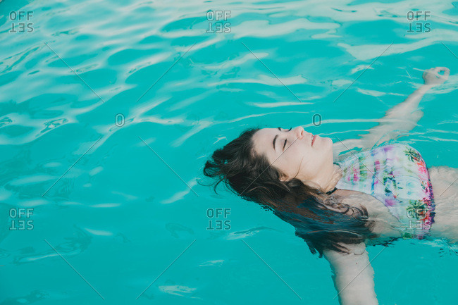 Relaxed girl inside the pool floating