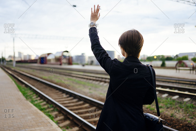 Woman waving hand leaving train