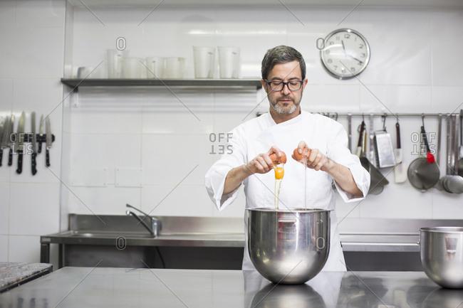 Chef breaking eggs in bowl