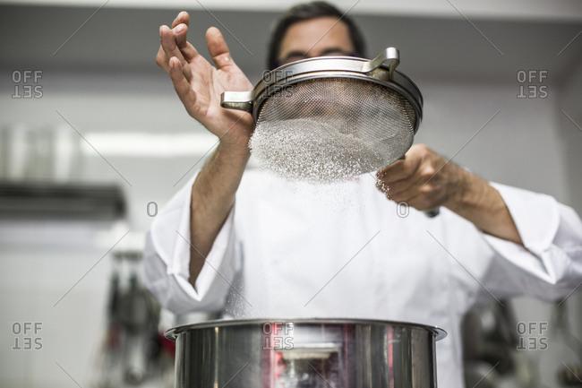 Chef sifting flour into bowl