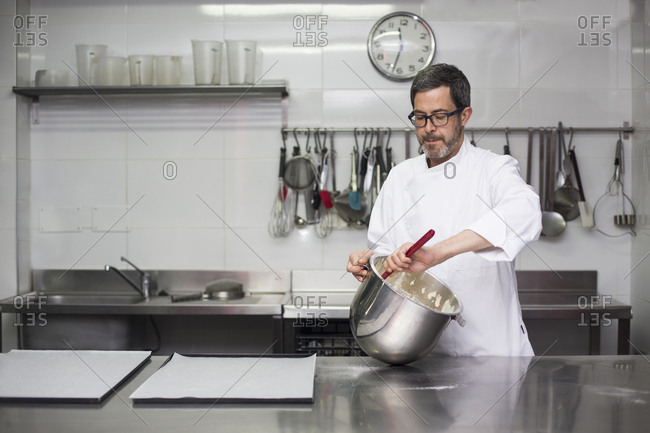 Chef kneading dough in bowl working in modern kitchen