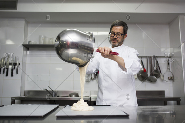 Chef putting dough out of bowl on cooking tray