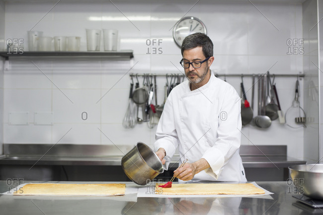 Chef soaking biscuit with syrup making pastry