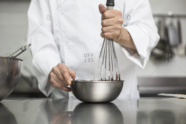 Chef whipping cream with whisk in bowl