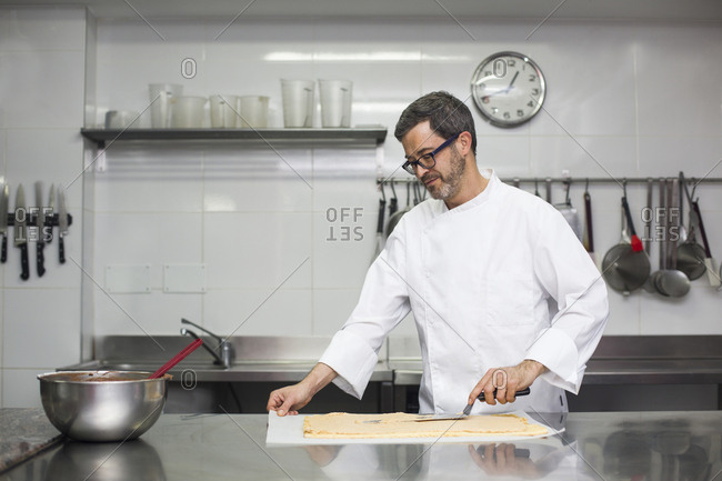 Concentrated chef spreading cream on biscuit layer