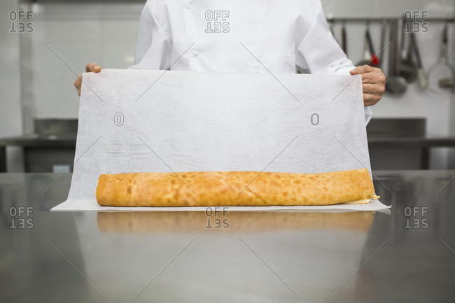Chef preparing pastry roll with baking paper
