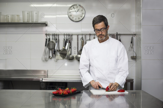 Chef slicing strawberries with kitchen knife