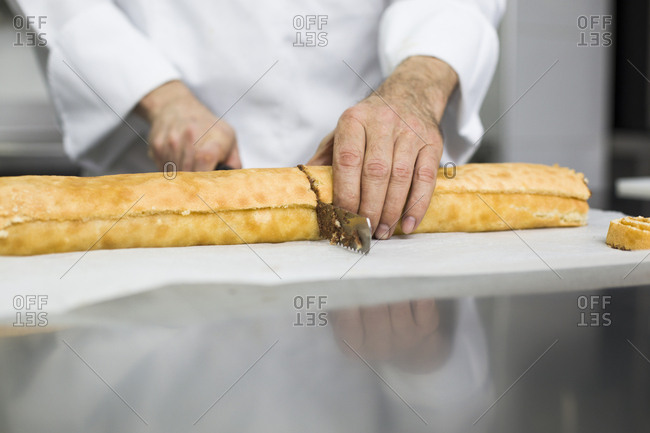 Chef cutting cake roll in portions