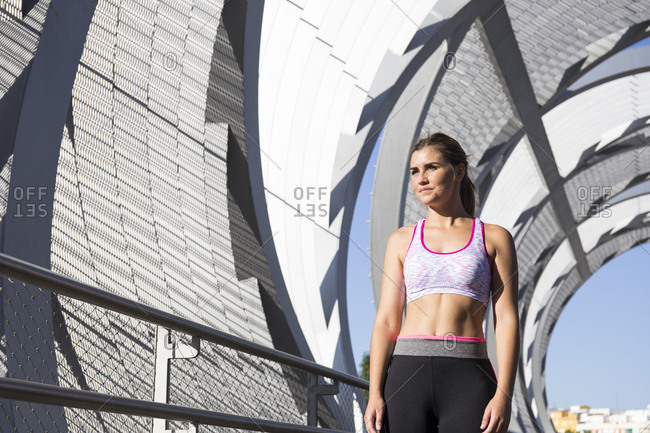 Young fit woman in sportswear standing in bright sunlight at street lo