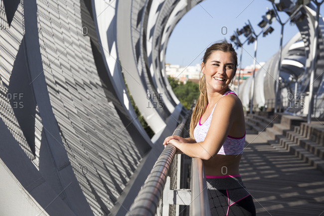 Beautiful girl in sportive clothing leaning on fence and laughing