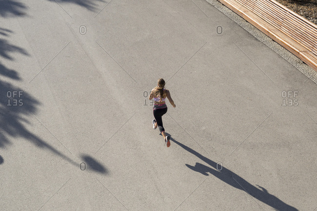 Aerial shot of sportswoman running on pavement in park in sunlight.