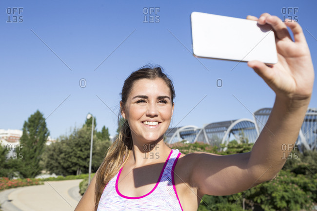 Young cheerful woman in sportive clothing posing and taking selfie wit