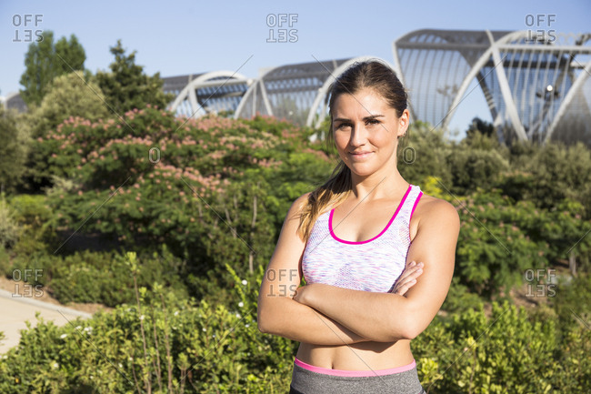Portrait of young woman in sportswear standing with hands crossed and