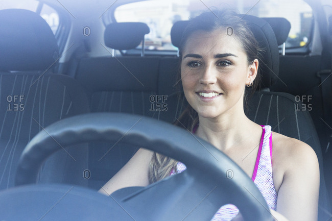 Young woman in sportive clothing driving car smiling and looking